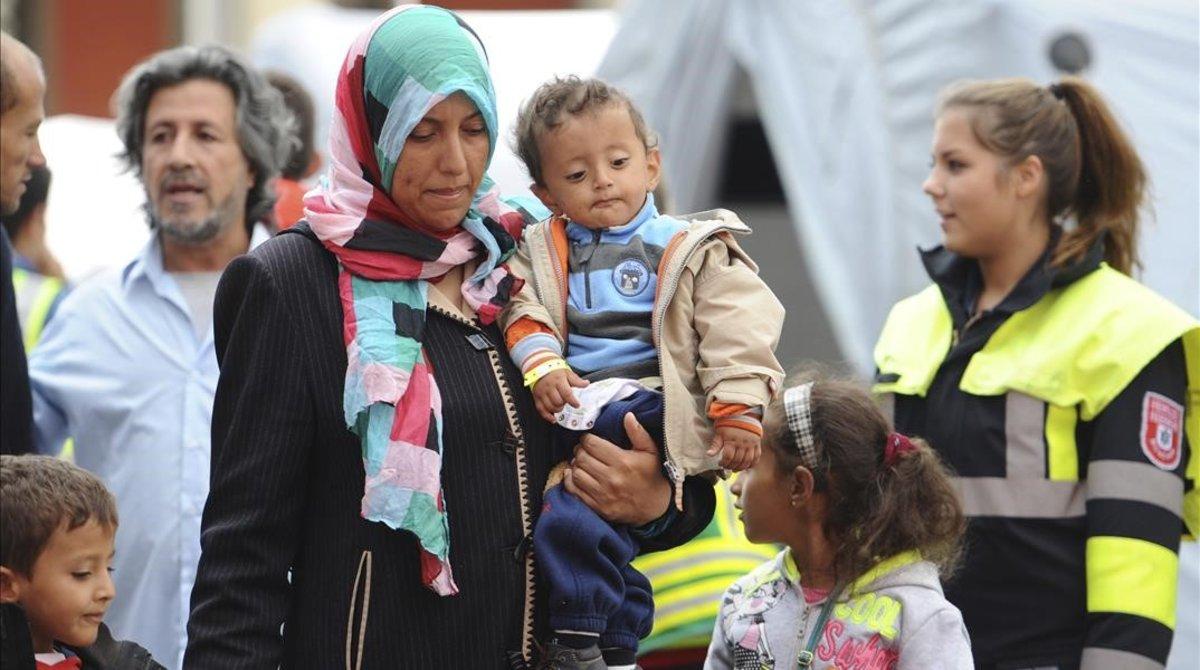 Una mujer y un niño, junto con otros migrantes y refugiados, son trasladados a un tren con destino a otra ciudad alemana poco después de su llegada a Múnich.