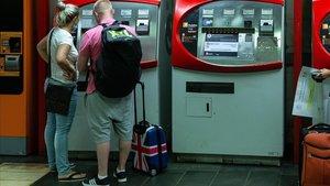 Una pareja de turistas británicos en la estacion de Renfe de Plaza Catalunya en Barcelona, este lunes.