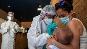 Una sanitaria realiza un test PCR a un niño en un espacio habilitado fuera de un Centro de Salud de la ciudad de Zaragoza, el pasado 1 de julio.