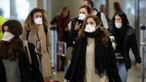 Viajeros procedentes de Italia protegidos con mascarillas a su llegada al aeropuerto de Manises (València), este martes.