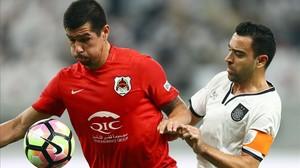 Xavi, ante el paraguayo Cáceres en la final de la Copa del Emir que ganó su equipo.