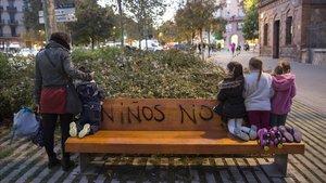 Varias niñas y una madre posan en el banco en el que un vecino compartió su odio a los niños, en Sant Joan