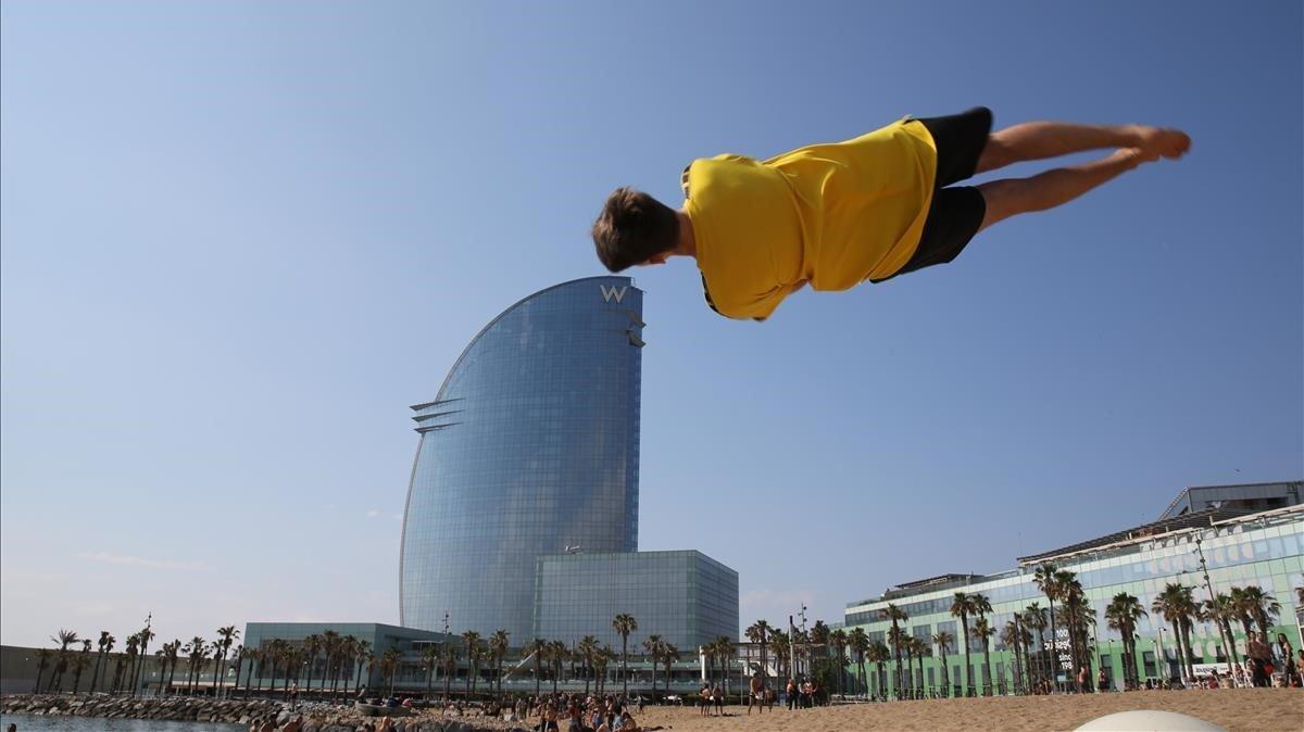 Un joven hace piruetas sobre la arena dela playa de Sant Sebastià, en la Barceloneta.