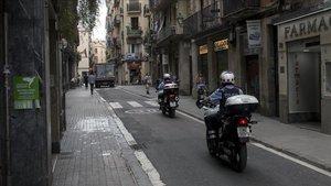 Una pareja de agentes de los Mossos d'Esquadra en motocicleta por el Raval de Barcelona este viernes al mediodía.