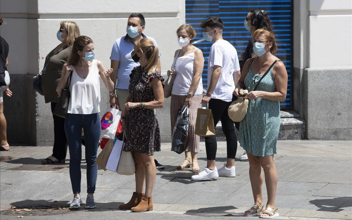 Varios ciudadanos con mascarilla pasean por las calles de Barcelona, este martes.