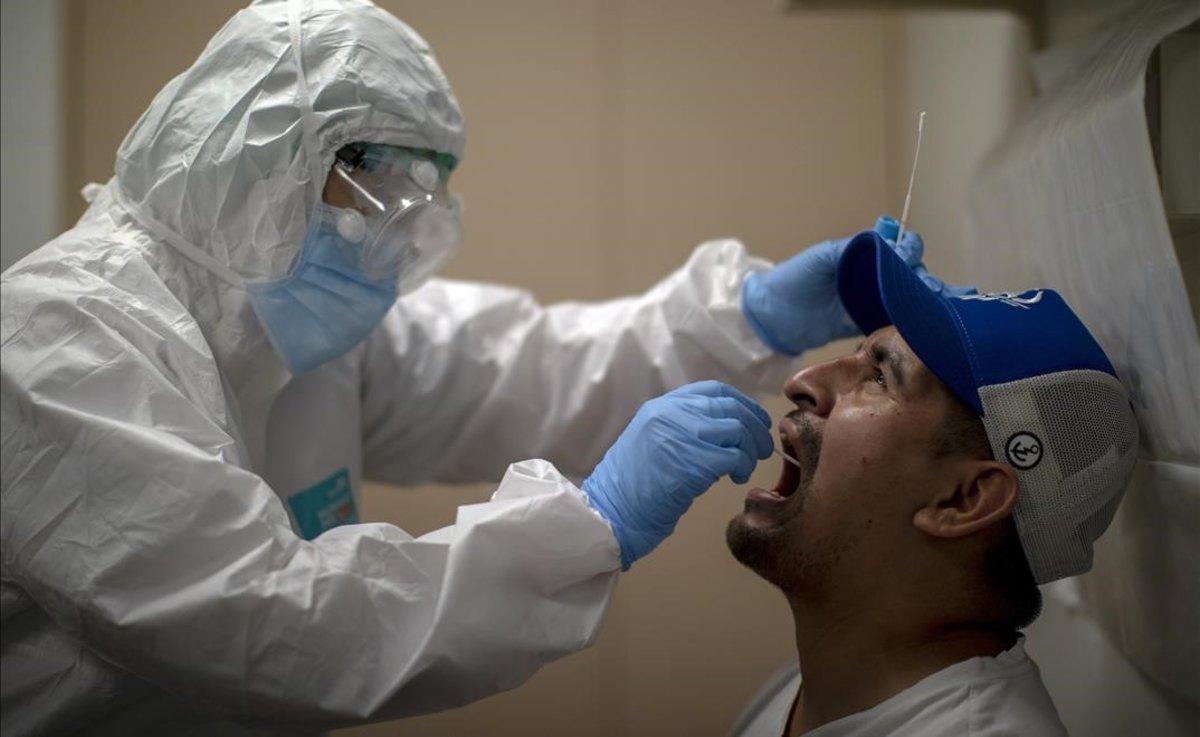 Un sanitario realiza un test de coronavirus en un centro de atención primaria de L'Hospitalet.