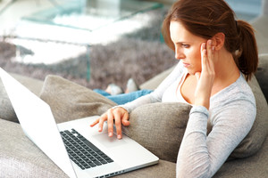 Portrait of pretty young woman working on laptop while sitting on sofa at home