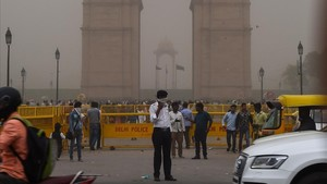Un agente de policía de Nueva Delhi dirige el tráfico mientras se cubre la cara en medio de una tormenta de arena.