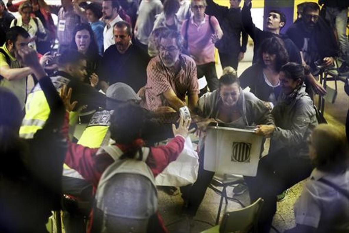 Agentes de la Policía Nacional se abalanzan sobre las urnas, en la escuela Ramon Llull de Barcelona.