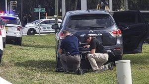 Agentes de policia se protegen tras su vehículo durante el tiroteo en el banco de Florida, este miércoles.