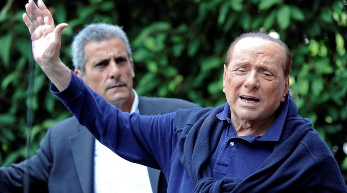 Berlusconi (derecha), al salir del hospital tras operarse del corazón, en Milán, el 5 de julio del 2016.