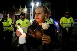 Ciudadanos y policias participan en un planton frente a la Escuela de Cadetes de Policia General Francisco de Paula Santanderen BogotaColombiapara recordar a quienes murieronen un atentado perpetrado con un carro bomba EFE Leonardo Munoz