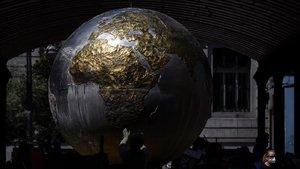 Una mujer con mascarilla pasea junto a una escultura de la bola del mundo durante el quincuagesimo quinto dia de confinamiento en la ciudad de Valladolid.