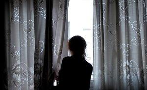Una mujer mira por la ventana de su casa, en la que permanece confinada.