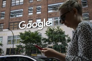 NEW YORK NY - JUNE 3 A woman looks at her smartphone as she walks past Google Building 8510 at 85 10th Ave on June 3 2019 in New York City Shares of Google parent company Alphabet were down over six percent on Monday following news reports that the U S Department of Justice is preparing to launch an anti-trust investigation aimed at Google Drew Angerer Getty Images AFP FOR NEWSPAPERS INTERNET TELCOS TELEVISION USE ONLY