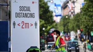 Un cartel en Londresque recuerda la distancia social requerida hasta ahora en el Reino Unido y ha pasado de dos a un metro.