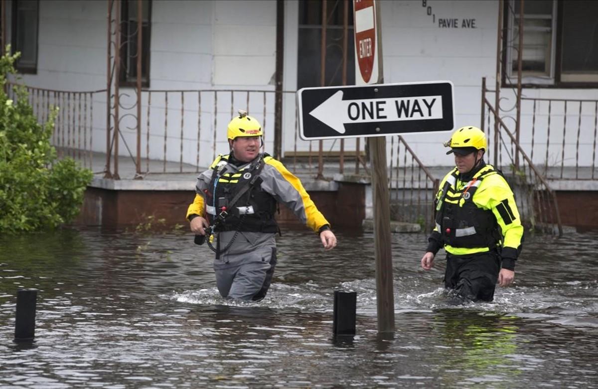 Dos bomberos de Greenville tratan de desplazarse por las calles anegadas de esta localidad estadounidense, una de las más afectadas por el huracán.
