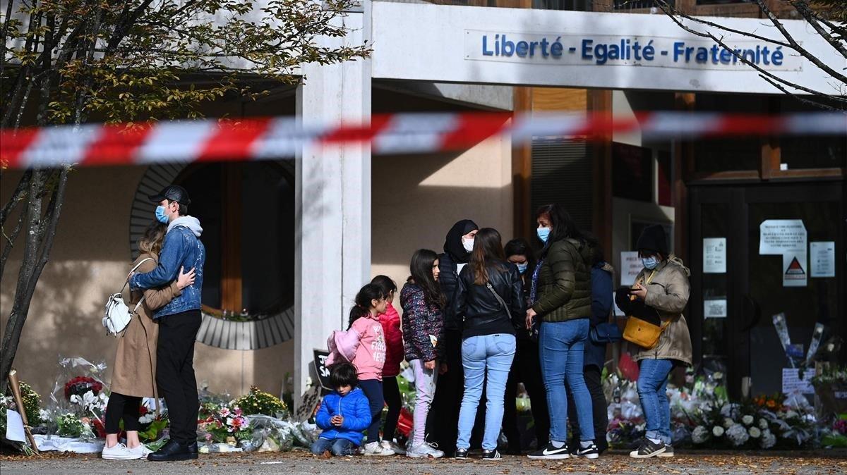 La gente coloca flores en los alrededores del centro de secundaria Bois d'Aulne en homenaje al maestro de historia asesinado Samuel Paty.
