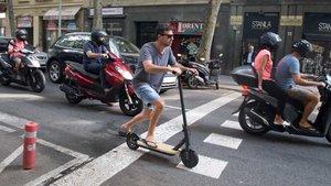 Un hombre conduce un patinete eléctrico por la calzada.