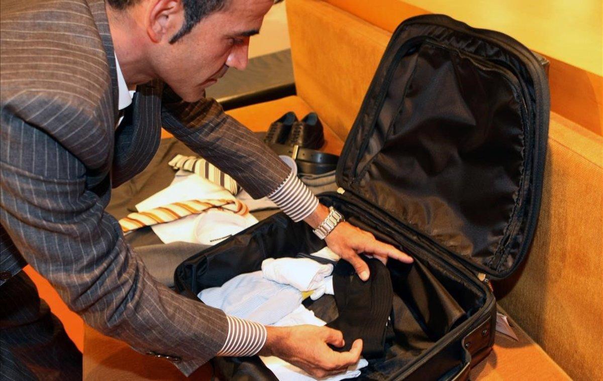 Hombre haciendo la maleta en un hotel.