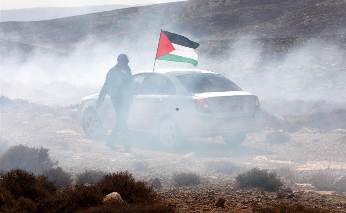 Un hombre ondea la bandera palestina entre gas lacrimogeno en el pueblo cisjordano de Shiyoukh.