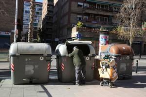 Un hombre recoge un pantalón de los contenedores, en Nou Barris.