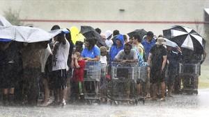 Un grupo de personas hacecola bajo unaintensa lluvia en una tienda de ultramarinos en Carolina del Norte.
