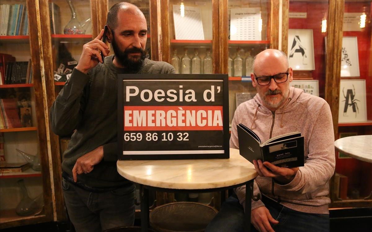 Edu Bernal y Fede Nieto posan con un cartel con el teléfono de emergenciaspoéticasen la entrada deL'Horiginal. Aquí se suele intercambiar el móvil los miércoles entre voluntarios.