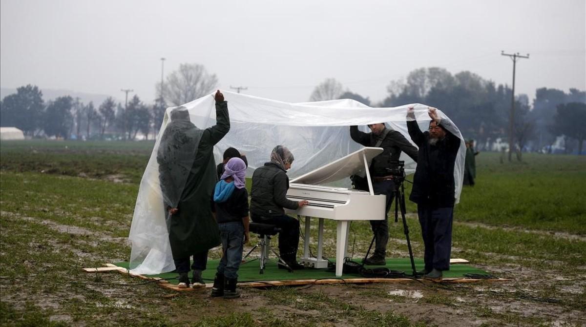 La joven siria Nour Alkhzam toca el piano blanco instalado en el campamento.