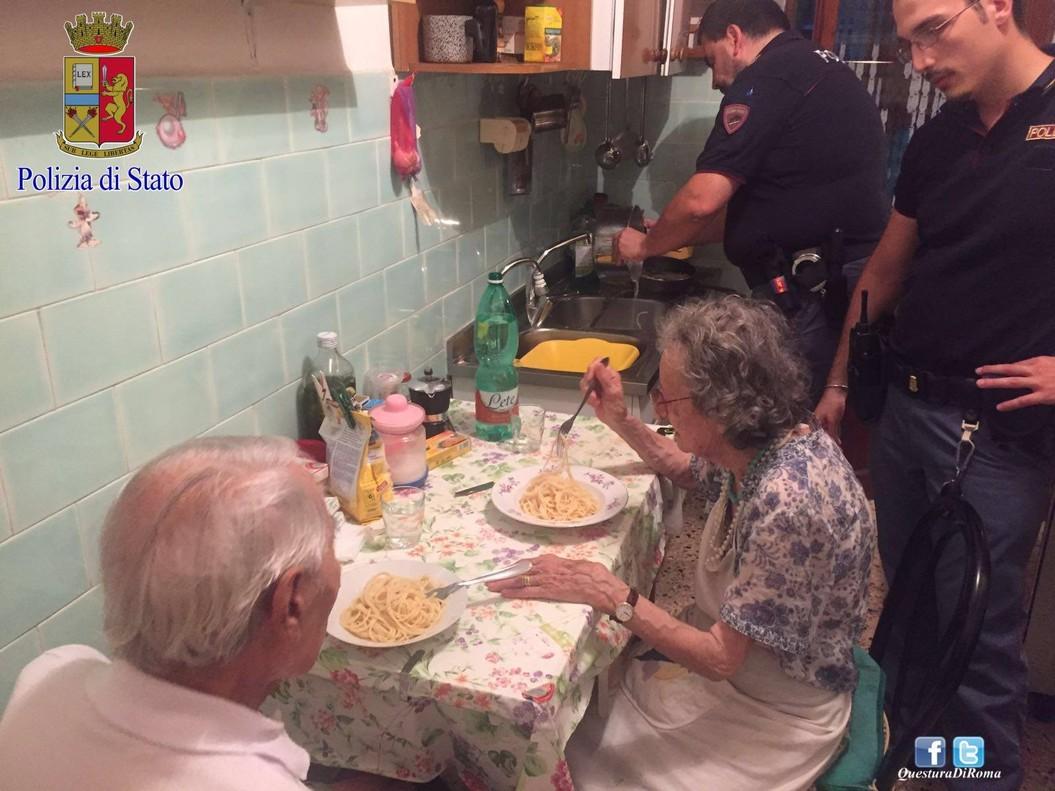 Michele, de espaldas, y Jole comen el plato de pasta que les han preparado los agentes de la policía de Roma.