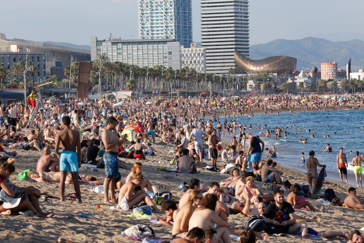 Muchísimos turistas disfrutan del verano en la plaza de la Barceloneta.