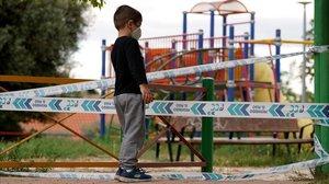 Un niño, frente a un parque infantil en Madrid que reabre este lunes.