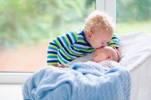 Niño pequeño besando a su hermano recién nacido.