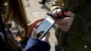 Adolescentes con un móvil en Barcelona