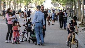 Padres pasean por sus hijos por una calle peatonal de París, este domingo.