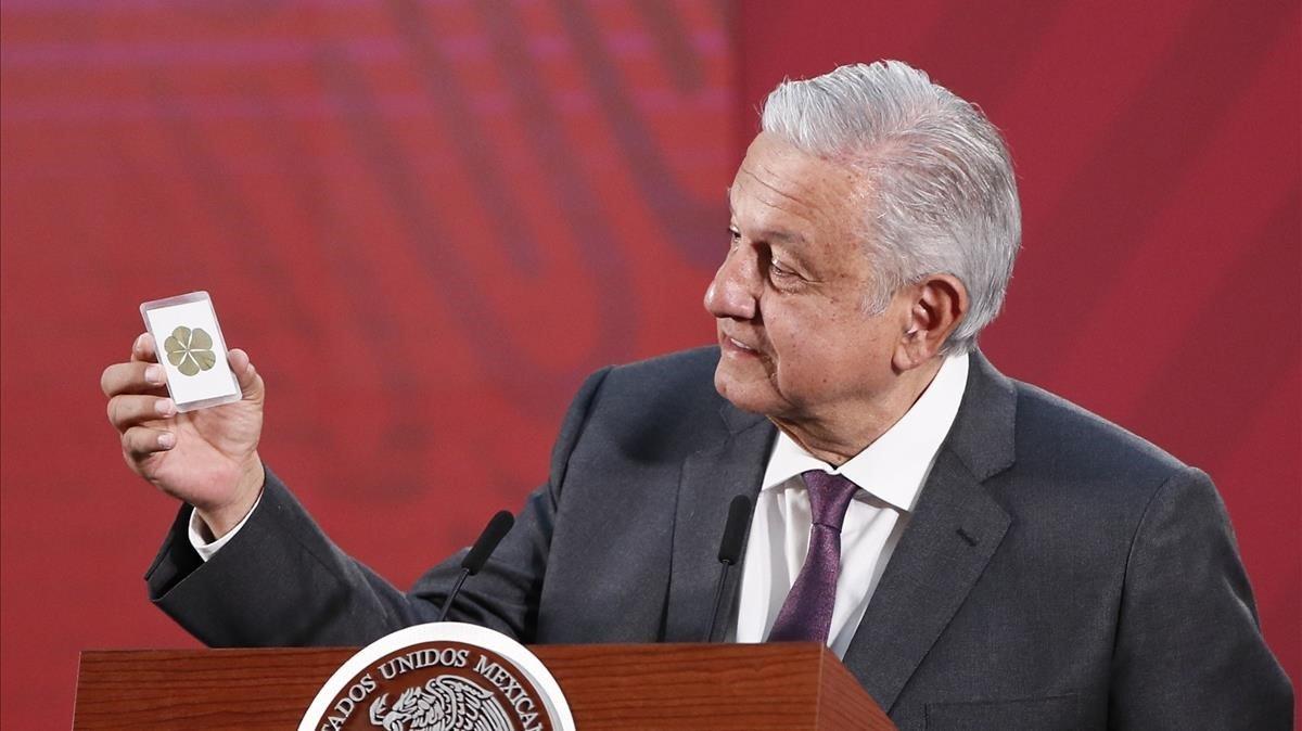 El presidente de México, Andrés Manuel López Obrador, muestra una estampa con un trébol de seis hojas durante una rueda de prensa el pasado 19 de marzo.
