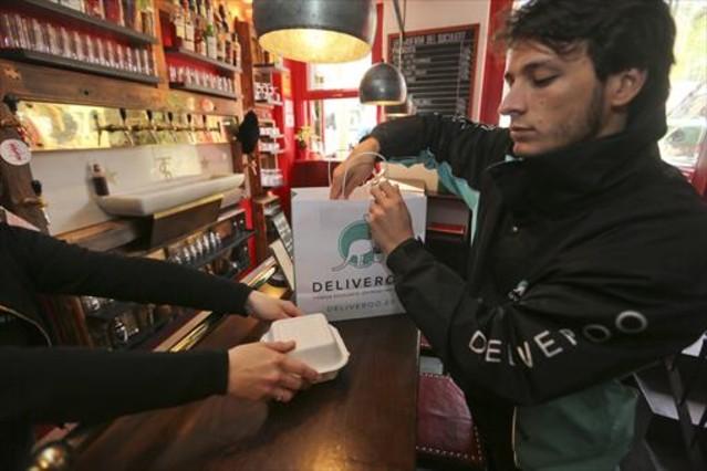 Un repartidor de Deliveroo recoge un pedido en La Taverna del Suculent.