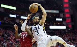Utah Jazz guard Ricky Rubio, right, is fouled by Houston Rockets guard Chris Paul, left, as he drives to the basket during the second half in Game 5 of an NBA basketball playoff series, in Houston, Wednesday, April 24, 2019. (AP Photo/David J. Phillip)