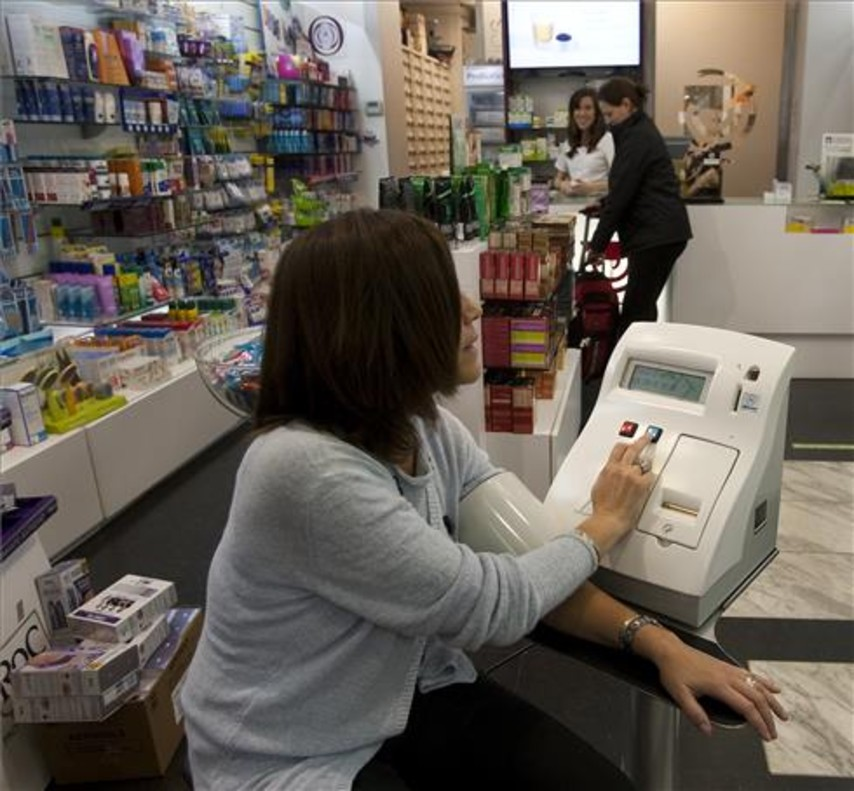 Una mujer se toma la tensión en una farmacia.