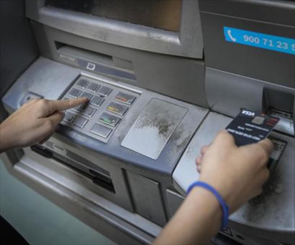 Servicio 8Una clienta retira dinero en efectivo de un cajero, en Barcelona.