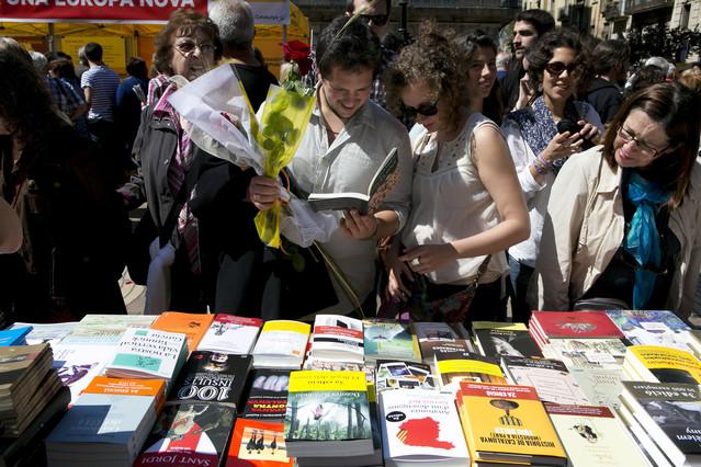 Una pareja se detiene frente a una parada de libros en Barcelona durante la diada de Sant Jordi.