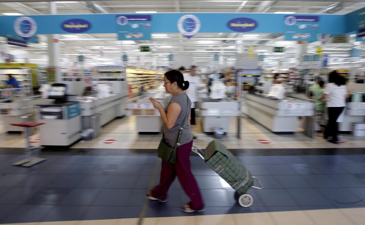 Una mujer camina con su carro de la compra ante la entrada de un hipermercado.