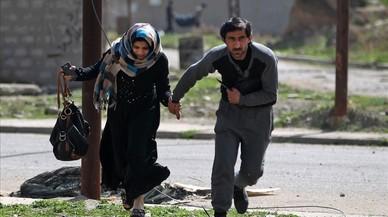 Una parella corre per protegir-se d'una ofensiva militar al barri d'Al-Tayaran de Mossul(Iraq).