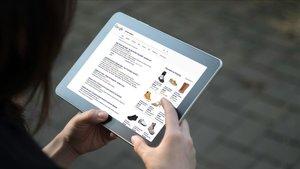 Una persona mira en una tableta entradas y fotos de Google.
