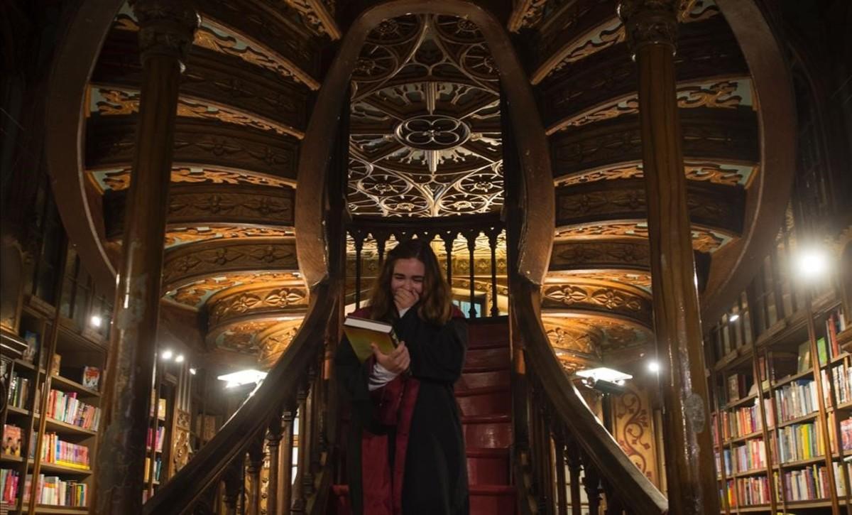 Una seguidora portuguesa, con el primer ejemplar recién adquirido del nuevo libro deHarry Potter, la noche del sábado al domingo en Oporto, en la escalinata de la célebre librería Lello, que inspiró a Rowling la atmósfera de la saga.