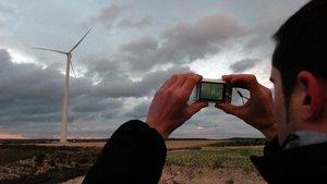 Un hombre fotografía una turbina eólica.