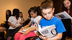 Unos niños leen el cuento 'Todos contra el vacío' en la presentación de la campaña 'Ningún niño sin bigote'.
