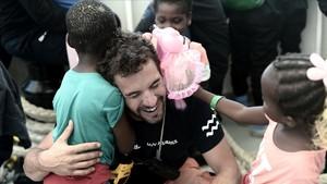 Un cooperante abraza a dos menores no acompañados tras el desembarco del Aquarius en Valencia.