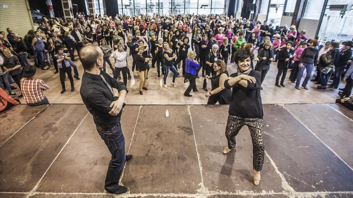 Enric Nonell yÀngels Guix, el domingo, sobre el escenario del centrocívicoCotxeres de Sants. El encuentro de line dance reunió a 450 aficionados y 60 profesores.