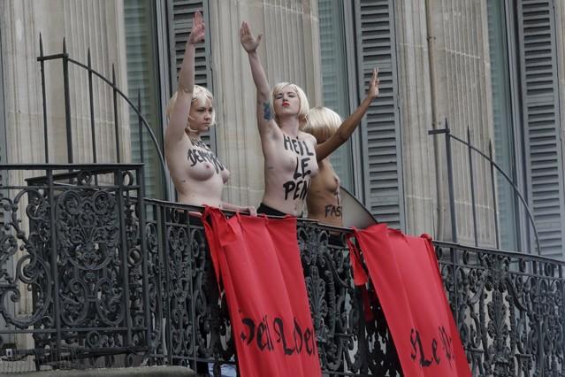 Activistas de Femen hacen el saludo nazi frente al lugar donde Marine Le Pen daba un discurso, este viernes en París.